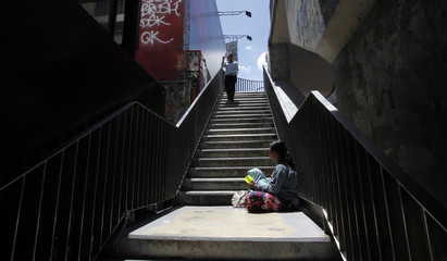 A homeless woman begs on a foot bridge in Bangkok