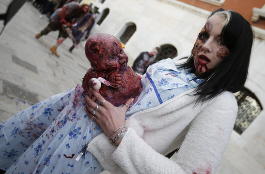 """A participant poses for a picture during a """"Zombie Walk"""", part of the Venetian Carnival, in Venice"""