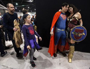 A young girl reacts as participants dressed in superhero costumes pose for a picture during the first edition of the HeroFestival in Marseille