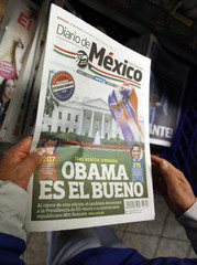 A consumer buys a newspaper written in Spanish, with Obama wining the U.S. presidential election on its frontpage, at a news stand in Times Square