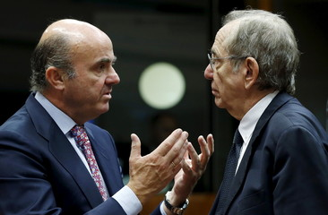 Spain's Economy Minister de Guindos talks to Italy's Finance Minister Padoan during a EU finance ministers meeting in Brussels