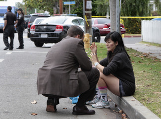 A police detective speaks to woman who has just been escorted from crime scene at Santa Monica College following shooting in Santa Monica