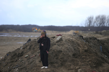 """A migrant stands on the top of a pile of sand which separates the road that leads to the ferry terminal and the camp known as the """"Jungle"""", a squalid sprawling camp in Calais"""