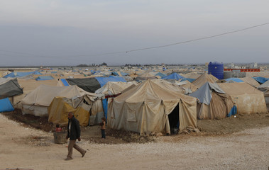 An internally displaced man walks past tents at the Bab Al-Salam refugee camp in Azaz, near the Syrian-Turkish border