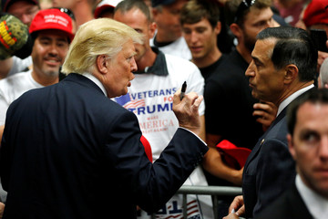 Republican U.S. presidential candidate Donald Trump speaks with U.S. Representative Darrell Issa after a rally with supporters in San Diego