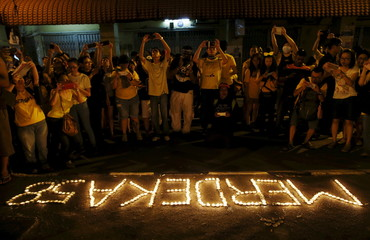 """Supporters of pro-democracy group """"Bersih"""" take photos of candle lights spelling """"Independence 58"""" just minutes into nation's 58th Independence Day in capital city of Kuala Lumpur"""