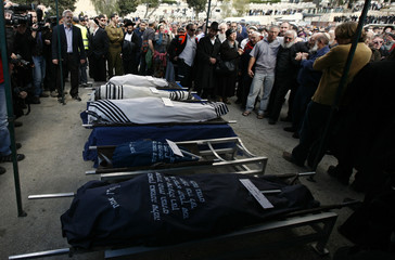 Mourners stand around the bodies of Ehud Foge, his wife Ruth and their children during their funeral in Jerusalem