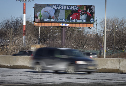 Cars drive past a billboard advertising the belief that marijuana is safer than alcohol or football alongside a highway in Newark