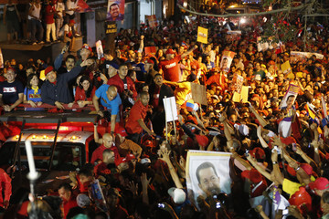 Venezuelan President and presidential candidate Chavez greets supporters from his vehicle during a campaign rally in Caracas
