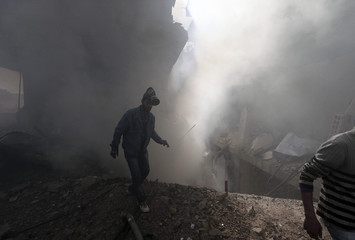 A man walks in front of a burning building after a Syrian Air force air strike in Ain Tarma neighbourhood of Damascus