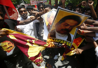 Supporters of MDMK, a regional political party, burn posters of Sri Lanka's President Rajapaksa and Sri Lankan flag during a protest against his visit  in New Delhi