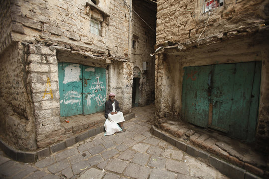 A man sits next to closed shops in the Old City of Ibb, the provincial capital of Yemen's central province of Ibb