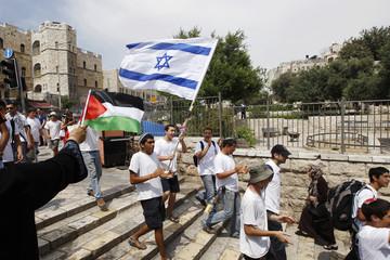 A Palestinian woman waves a Palestinian flag as Israeli youths celebrating Jerusalem Day walk past outside Jerusalem's Old City