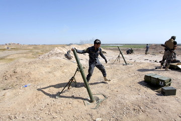 An Iraqi army soldier launches a mortar toward Islamic State militants in Tikrit