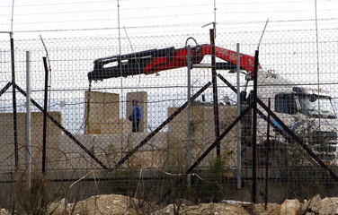 An Israeli worker oversees the establishment of a new wall as seen from the village of Kefar Kela toward the Israeli border in southern Lebanon