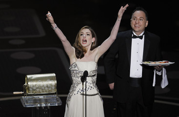 Hathaway gives away a plate of sushi during the 83rd Academy Awards in Hollywood
