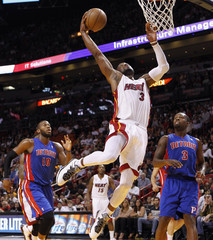Miami Heat's Wade shoots in front of Detroit Pistons' Monroe and Stuckey during NBA game in Miami