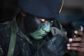 A Guatemalan Navy Special Forces soldier applies camouflage paint for a celebration to mark the founding anniversary of the Guatemalan Navy in Puerto Quetzal