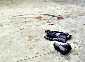 The equipment of a man believed to be the suspect in a shooting incident at Santa Monica College lies on the sidewalk after he was shot in Santa Monica