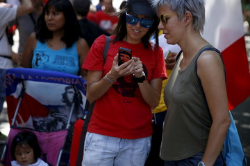"""Women check a phone displaying the image of revolutionary Ernesto """"Che"""" Guevara as they take part in a march marking the 62nd anniversary of the July 26, 1953 rebel assault on the Moncada military barracks in central Madrid"""