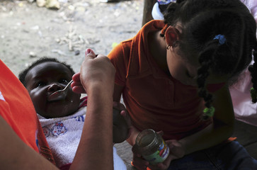 A Haitian Dominican baby is fed by neighbours in El Arenoso in Tamboril