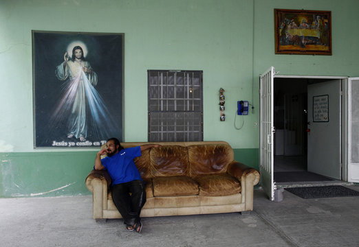 A man sits on a couch at Casa del Migrante in Reynosa, Mexico