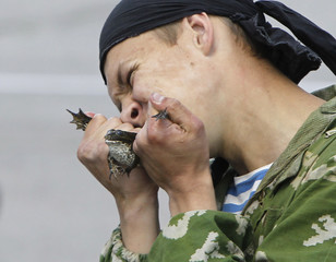 A Ukrainian paratrooper eats a live frog during a military show in Zhytomyr