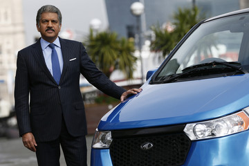 Anand Mahindra, chairman and managing director of Mahindra Group poses with a Mahindra e2o electric car during its launch in London