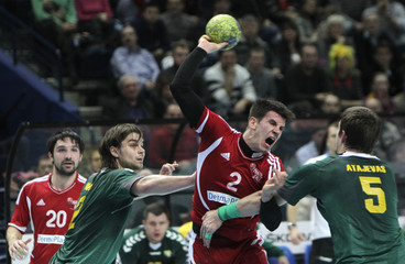 Schmid of Switzerland fights with Atajevas and Novickas of Lithuania during their men's handball World Championship 2013 qualification game in Vilnius