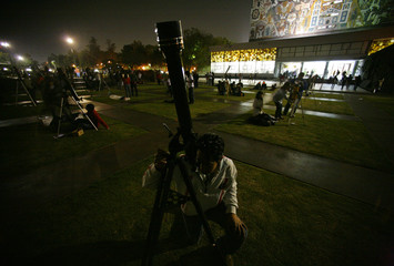 A man looks at the moon through a telescope in Mexico City
