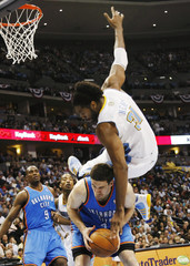 Denver Nuggets' Nene flips over Oklahoma Thunder's Collison during their NBA Western Conference basketball playoffs in Denver