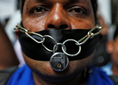 A journalist wears chain and lock around his mouth during a protest in front of Bombay House, headquarters of Tata Group, against the assault on journalists by the company's private security guards last week, in Mumbai