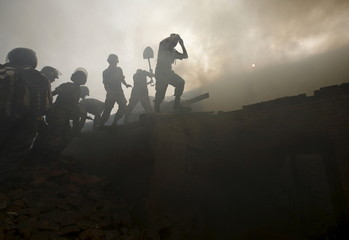 Members of the Nepalese Army work to put out a fire which broke out at the Nepal Electricity Authority (NEA) distribution center at Ratnapark in Kathmandu