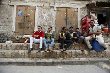 People sit on the side of a street in Yemen's capital Sanaa