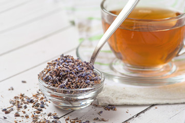 glass cup with natural lavender tea, flowers branch against violet linen background
