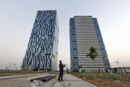 A worker folds cable of welding machine in front of two office buildings at Gujarat International Finance Tec-City at Gandhinagar, in Gujarat