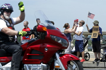 People look on with signs as riders take part in the Rolling Thunder First Amendment Demonstration motorcycle run on Memorial Day by crossing the Memorial Bridge leading from Arlington Cemetery into Washington