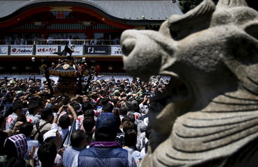 Local residents carrying a portable shrine are seen behind a stone carved guardian dog at the Kanda-Myojin shrine during the Kanda festival in Tokyo