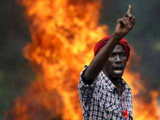 A protester gestures in front of a burning barricade during a protest against Burundi President Pierre Nkurunziza and his bid for a third term in Bujumbura