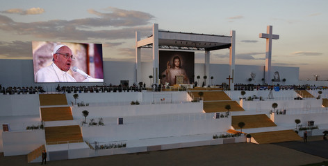 Pope Francis appears on a large screen as he prays during a vigil during World Youth Day in Brzegi near Krakow