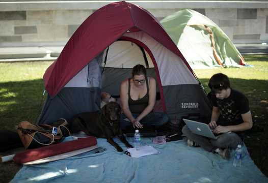 Natalia Abrams and Stephen Main work on their laptops at the Occupy LA protest camp in Los Angeles