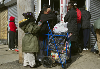 People wait outside a grocery store damaged by Hurricane Sandy to receive food and other supplies in the Rockaways section of the Queens borough of New York