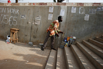 A man arranges books for sale on a pedestrian bridge where posters advertising jobs are pasted, in Ojodu district in