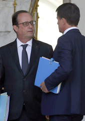 French President Francois Hollande and Prime Minister Manuel Valls speak after the first cabinet meeting following the summer break at the Elysee Palace in Paris