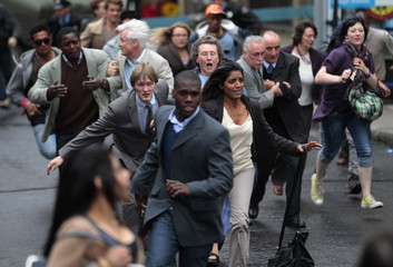 """Extras in the zombie movie """"World War Z"""" run along a street during filming in Glasgow, Scotland"""