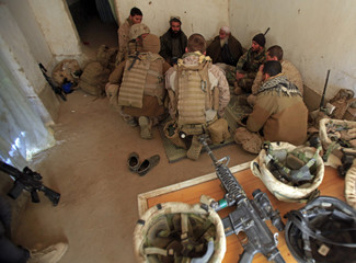 U.S. Marines talk to two civilians in the market of Karu Chareh in Marjah in Helmand province