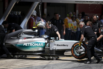 Mechanics push the car into the box of Mercedes F1 driver Rosberg of Germany during the qualifying session of the Spanish Grand Prix at the Circuit de Barcelona-Catalunya racetrack in Montmelo