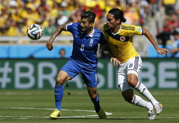 Greece's Kone fights for the ball with Colombia's Aguilar during their 2014 World Cup Group C soccer match at the Mineirao stadium in Belo Horizonte