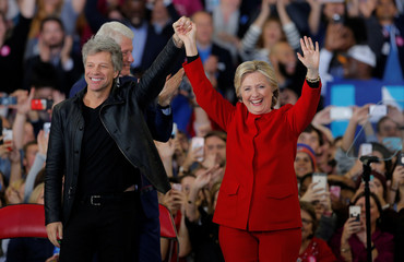 Democratic presidential nominee Hillary Clinton along with recording artist Jon Bon Jovi wave at a campaign rally in Raleigh