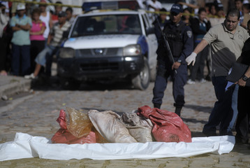 A forensic technician points at bags containing dismembered parts of a human bodies in a neighborhood in Tegucigalpa